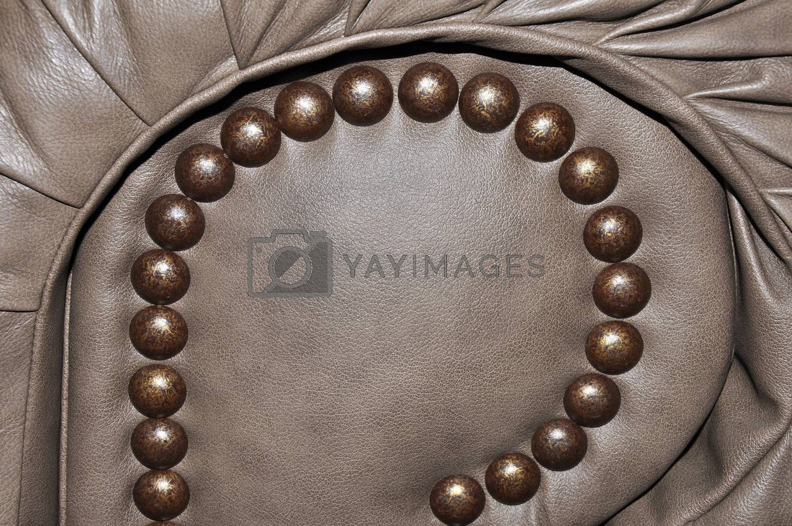 closeup view of tacks on a brown leather chair