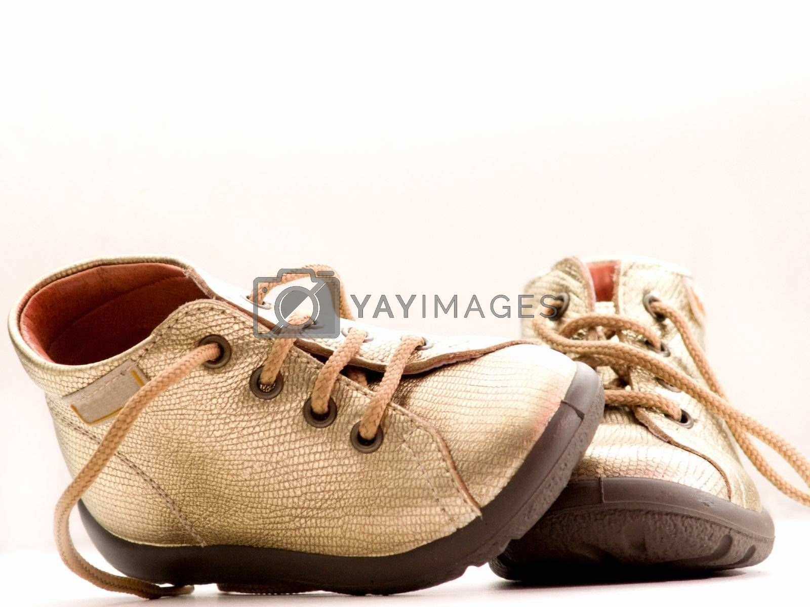 Royalty free image of Trendy little golden baby shoes  with copyspace by FreedomImage