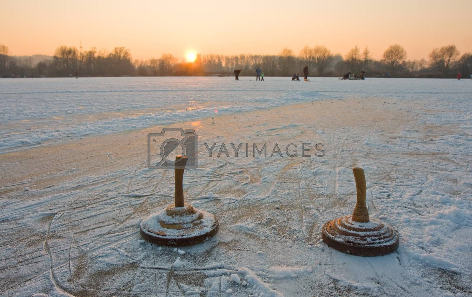 Royalty free image of two curling stones on a frozen lake at sunset by bernjuer