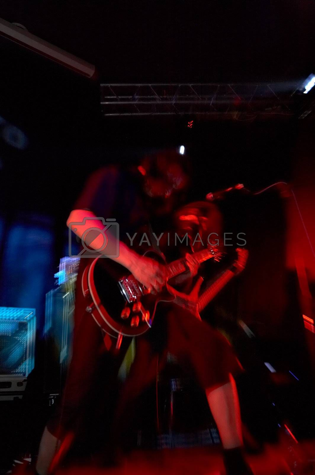 Royalty free image of Rock-guitarist on live concert with motion effect by DeusNoxious