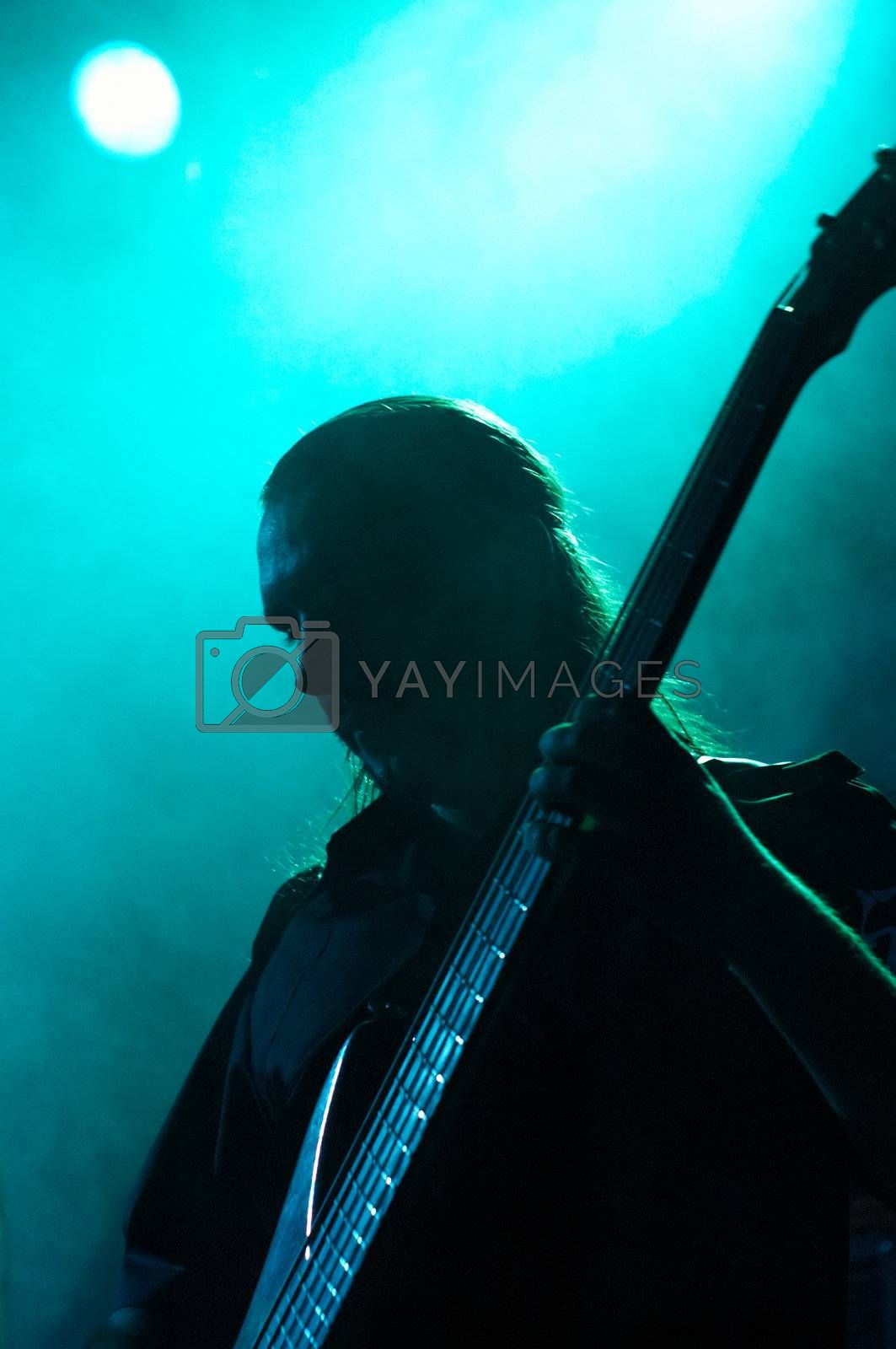 Royalty free image of Bass-guitarist on live convert, at bluelight with smoke by DeusNoxious