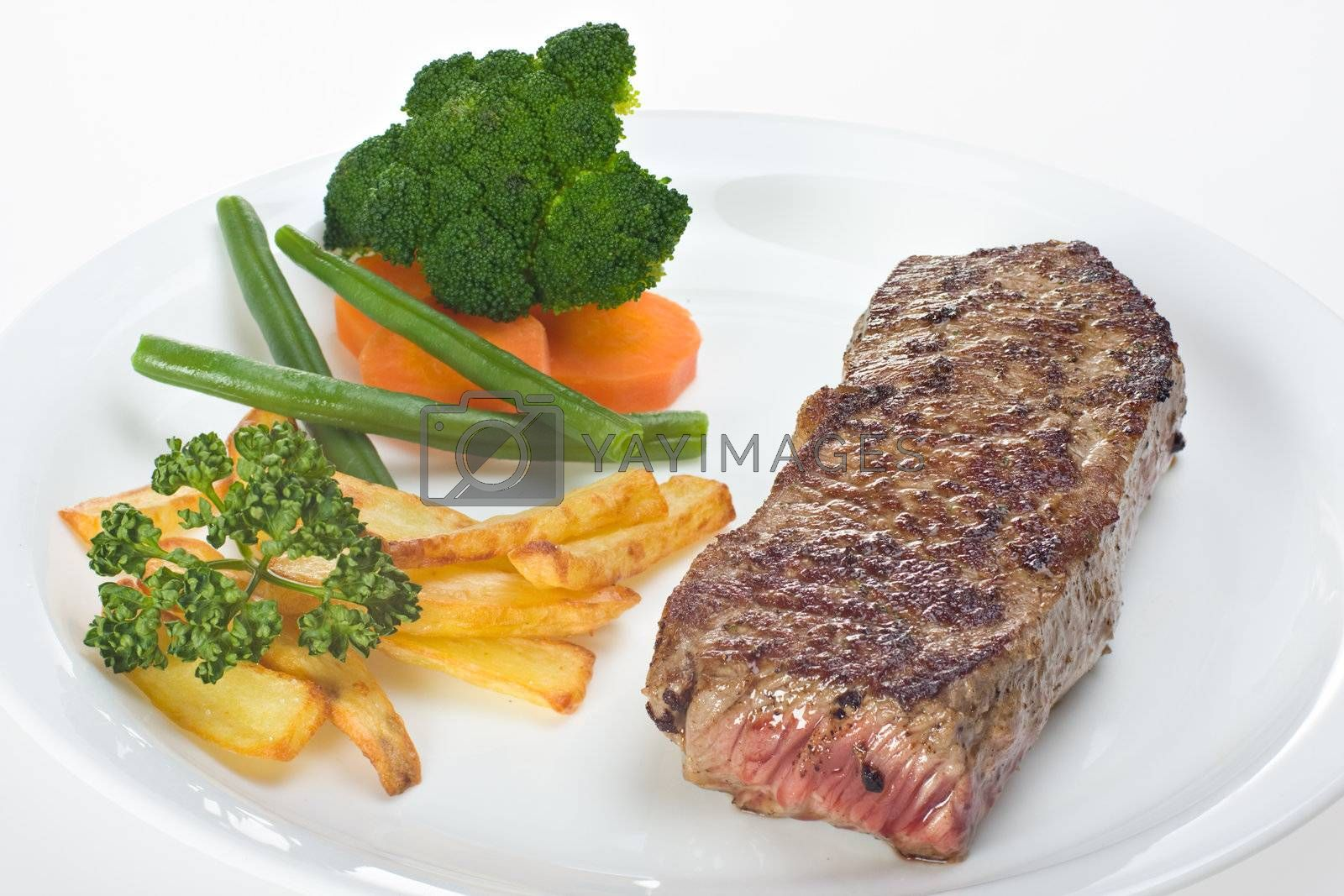 Royalty free image of grilled steak on a plate with fries by bernjuer