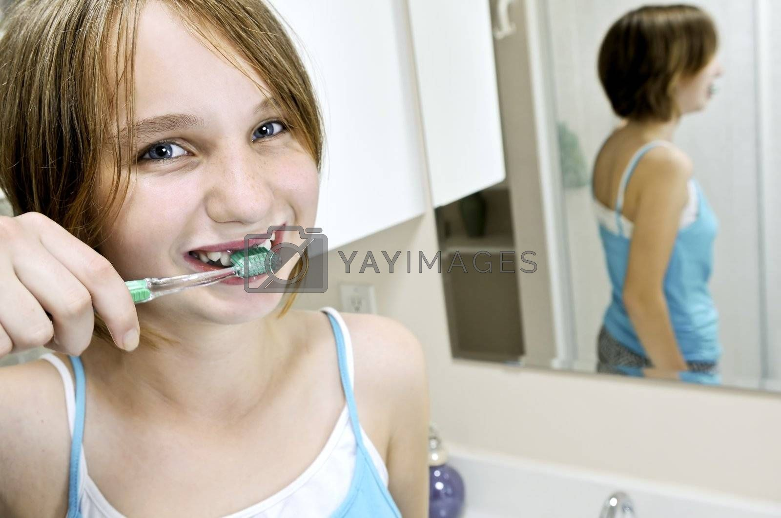Young girl brushing her teeth in a bathroom