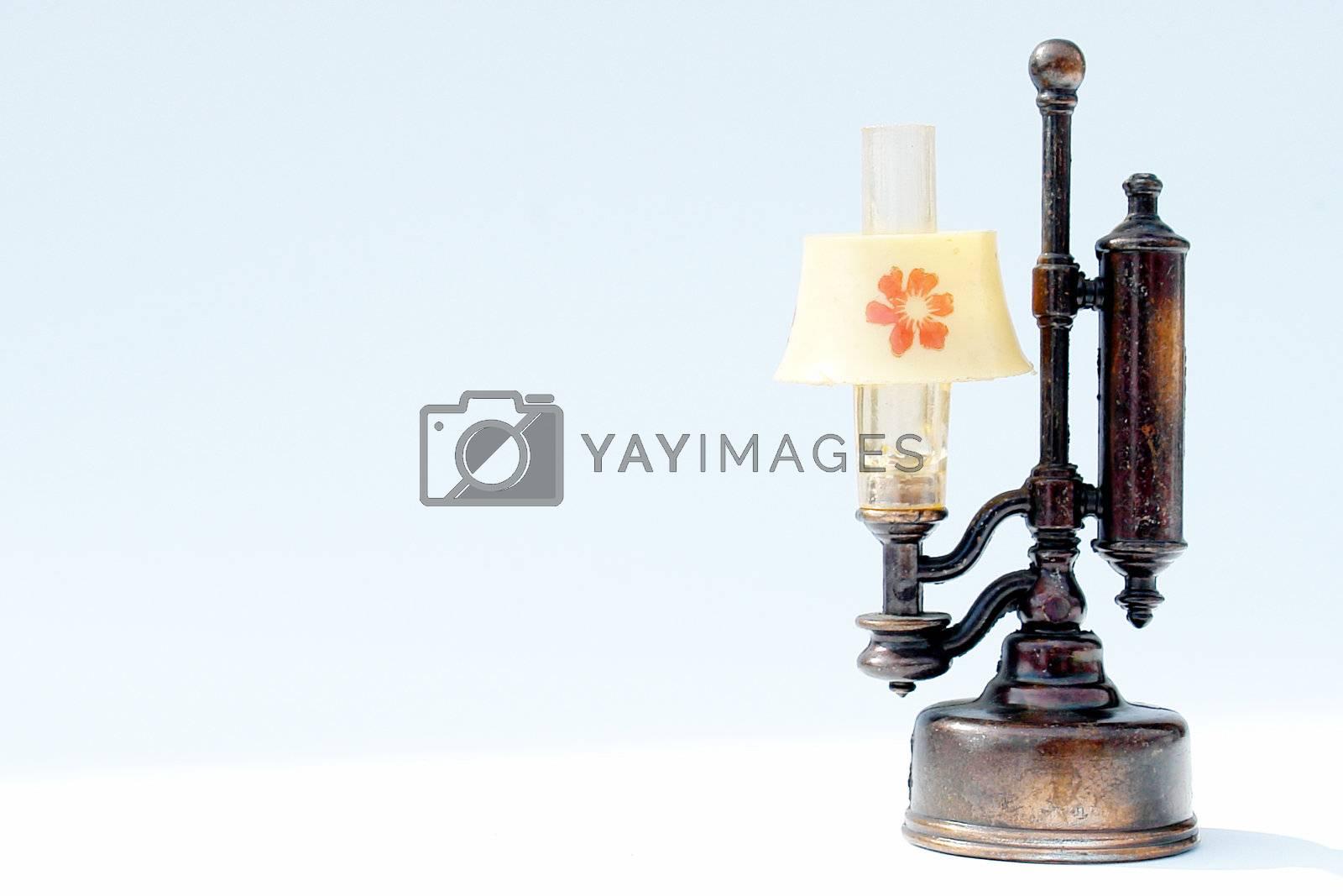 black antique lamp on white background with orange flower