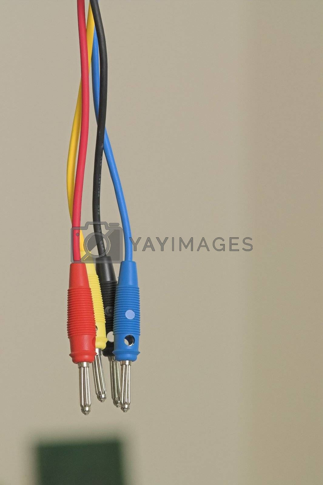 A tangle of interwoven male connectors against a wall and a circuit in the background.