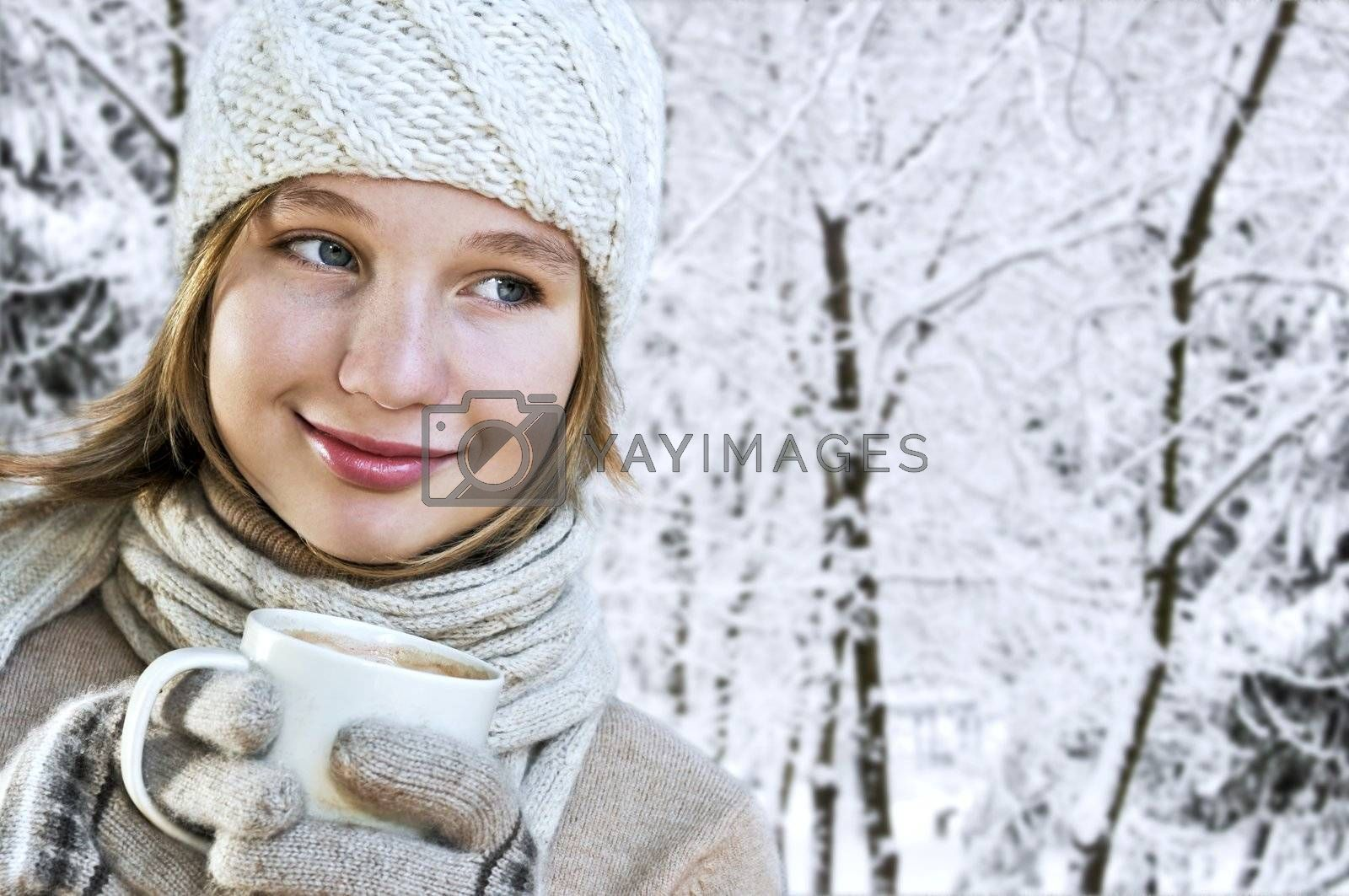 Teenage girl in winter hat with cup of hot chocolate
