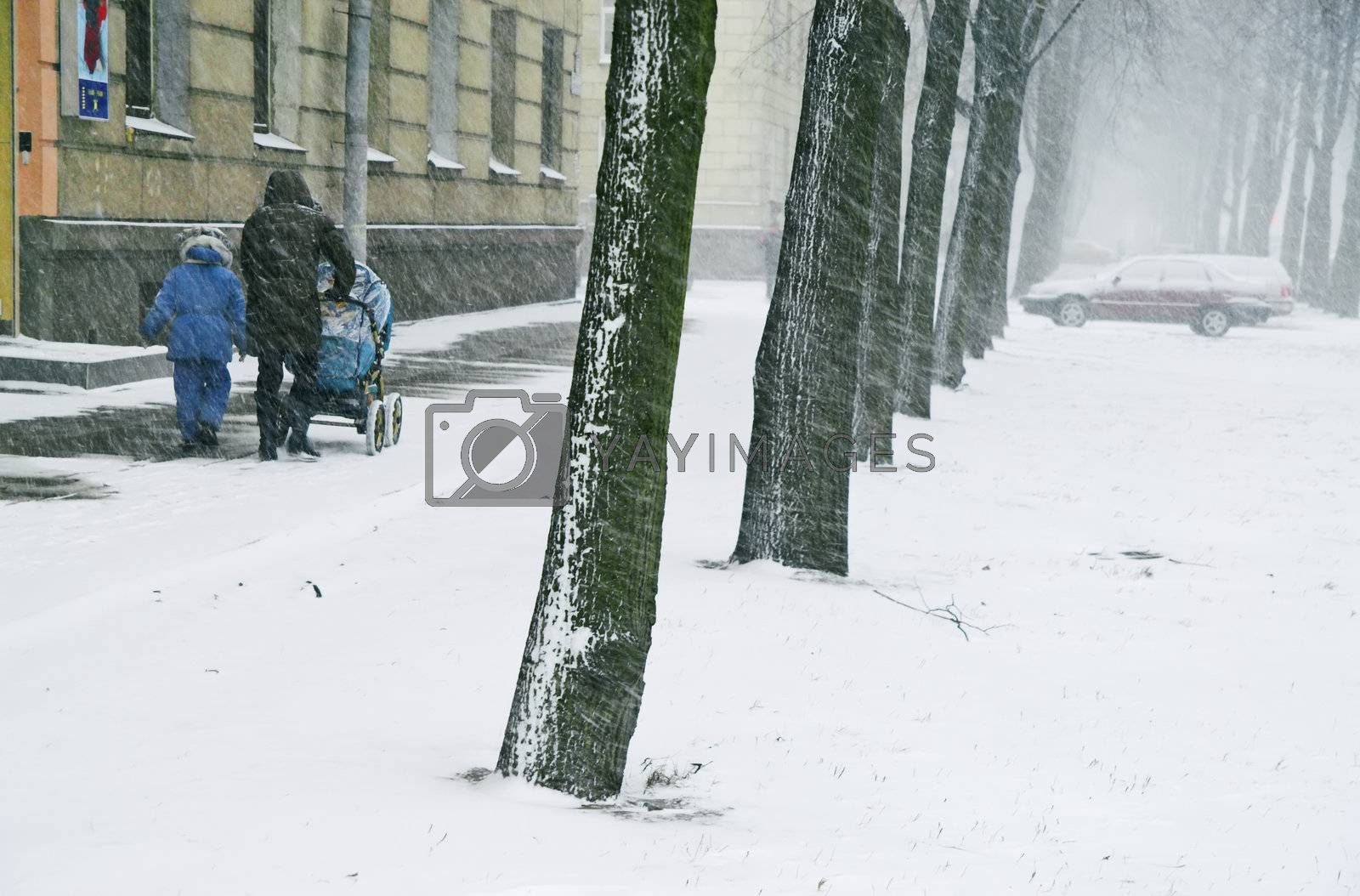 Mother with children walks along street in stormy weather