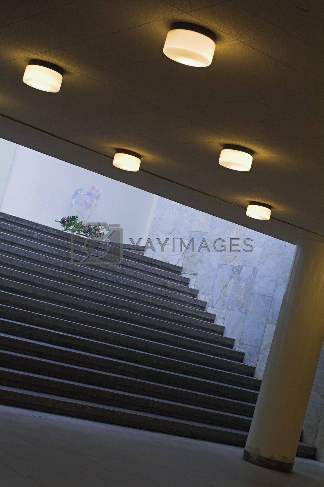 A staircase to a building's ground floor with lights on, a column, and a flower-bed in the natural light backgorund.
