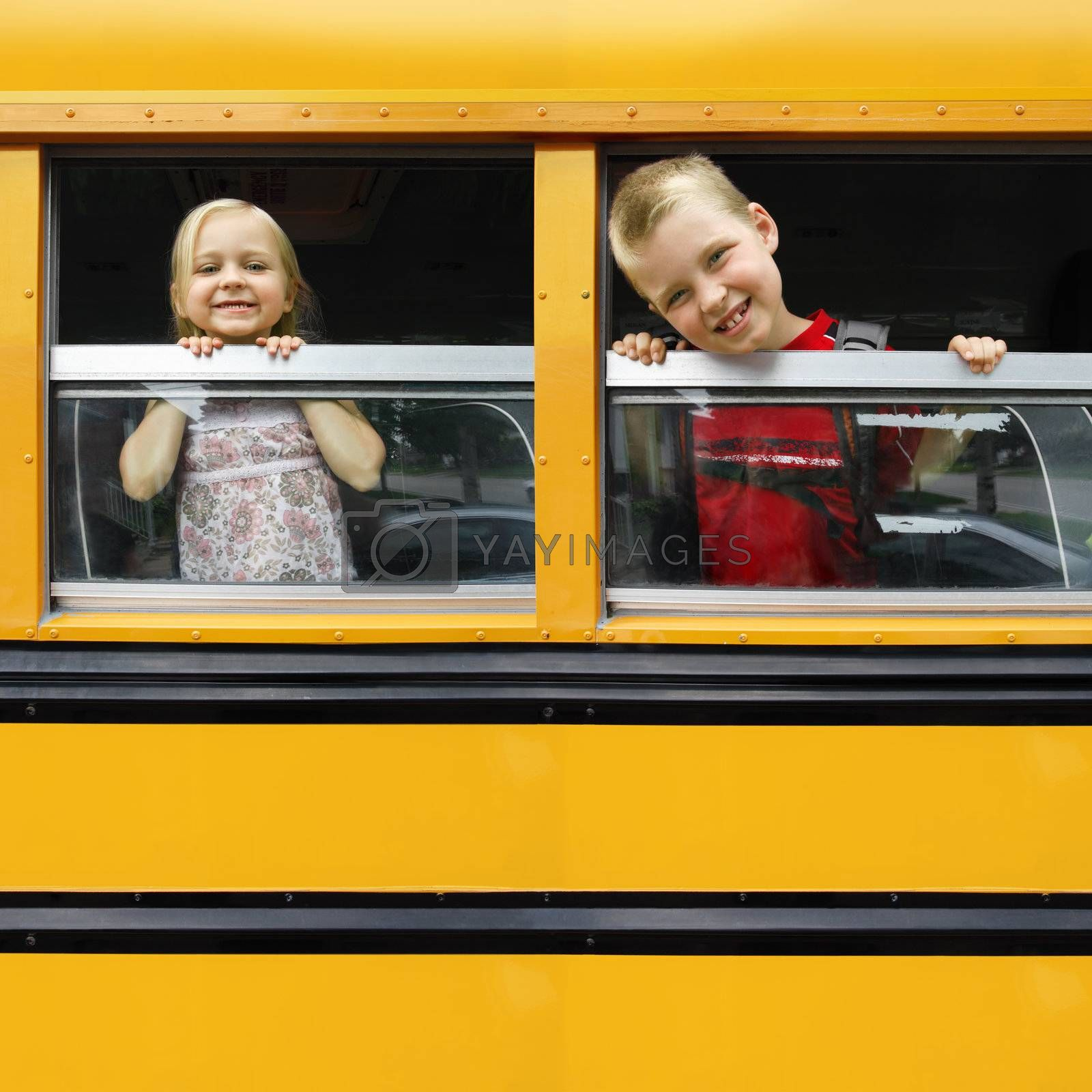 Photo of two happy children looking out the windows of a yellow school bus. Plenty of space for text.