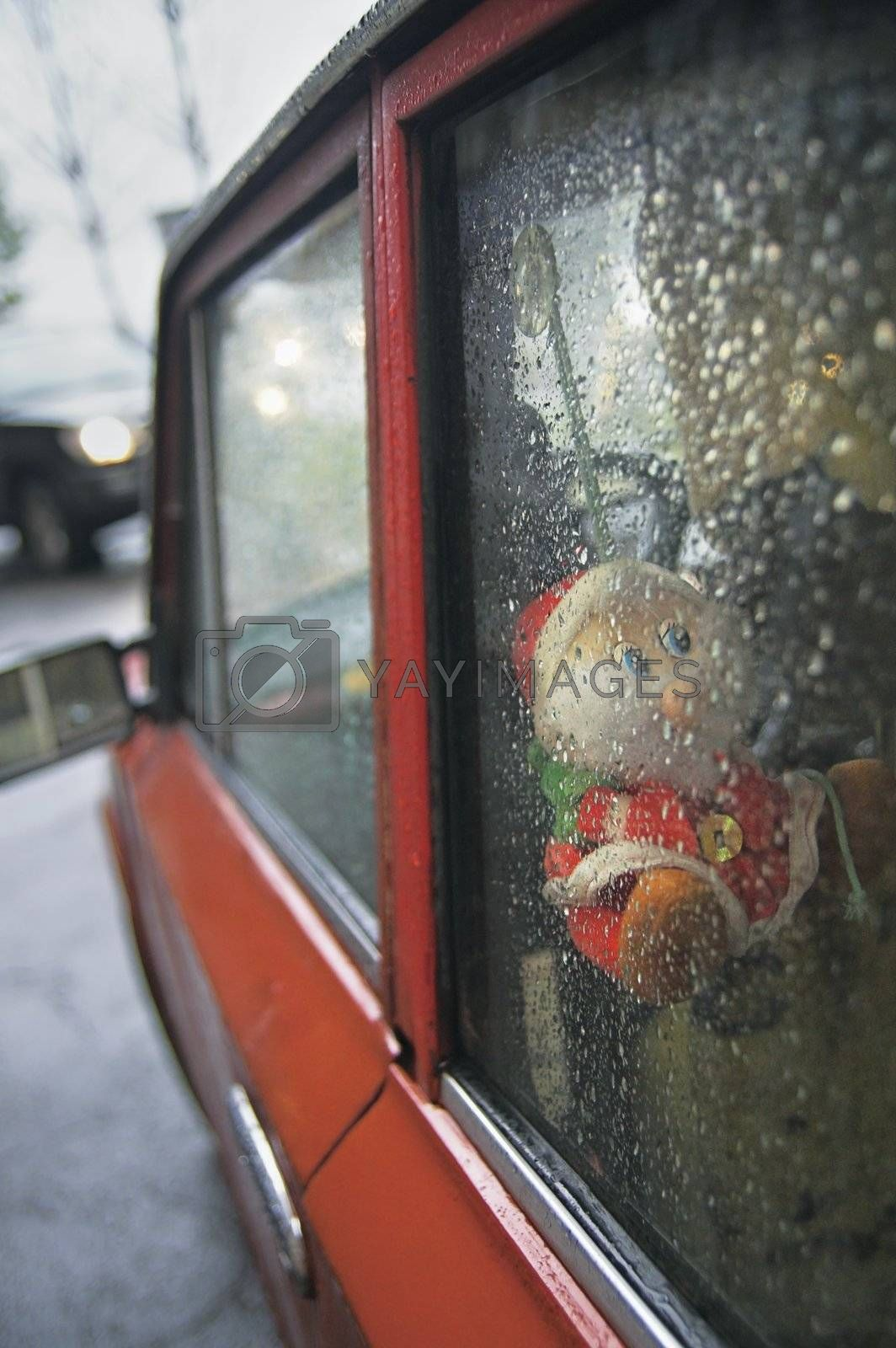 Dwarf toy viewed through car window while raining