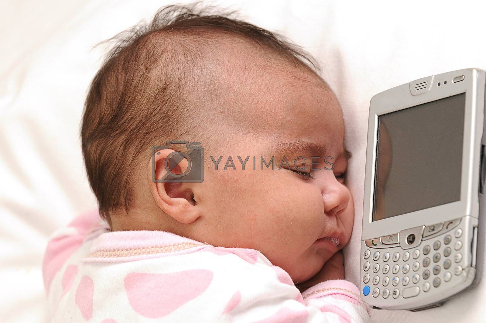 infant baby sleeping next to a mobile phone