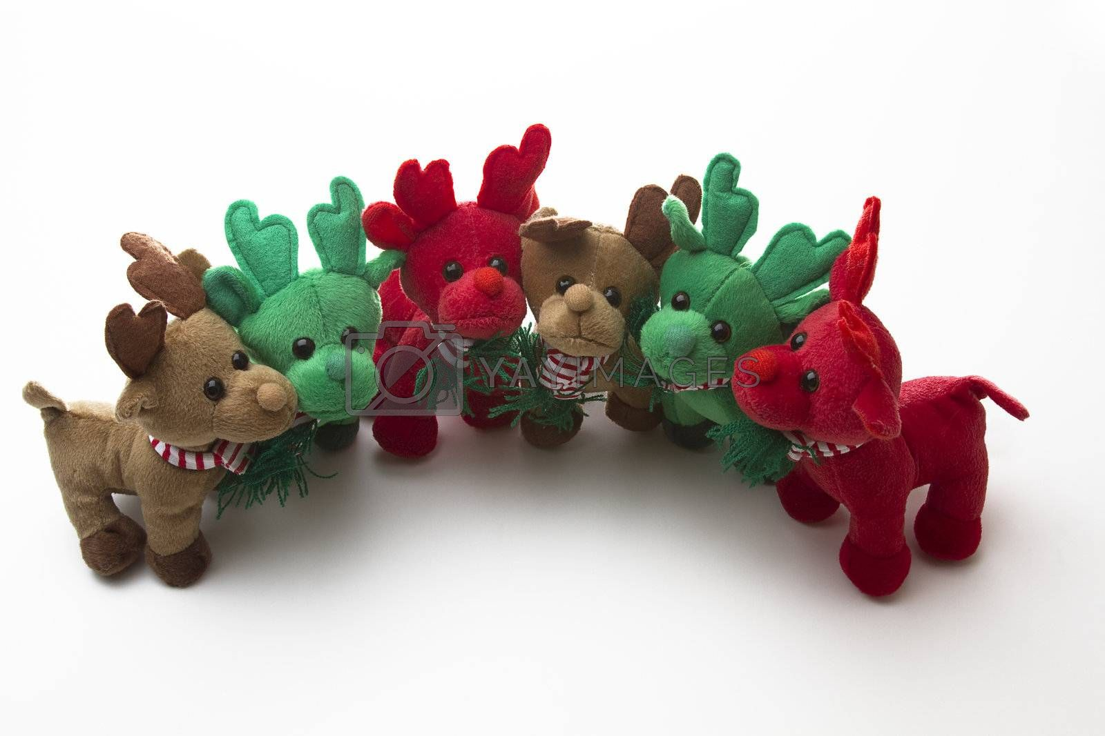 brown, green and red reindeer stuff toy, all close together in a half circle for group shot