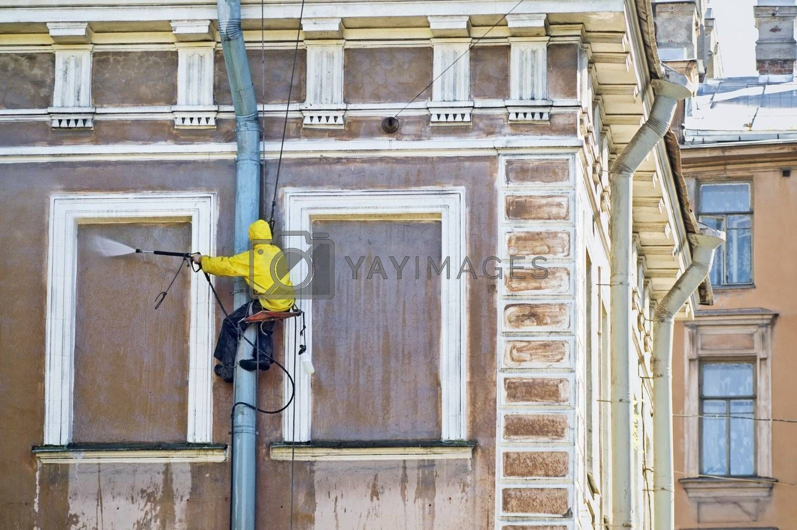 Cleaning service worker washing old building facade