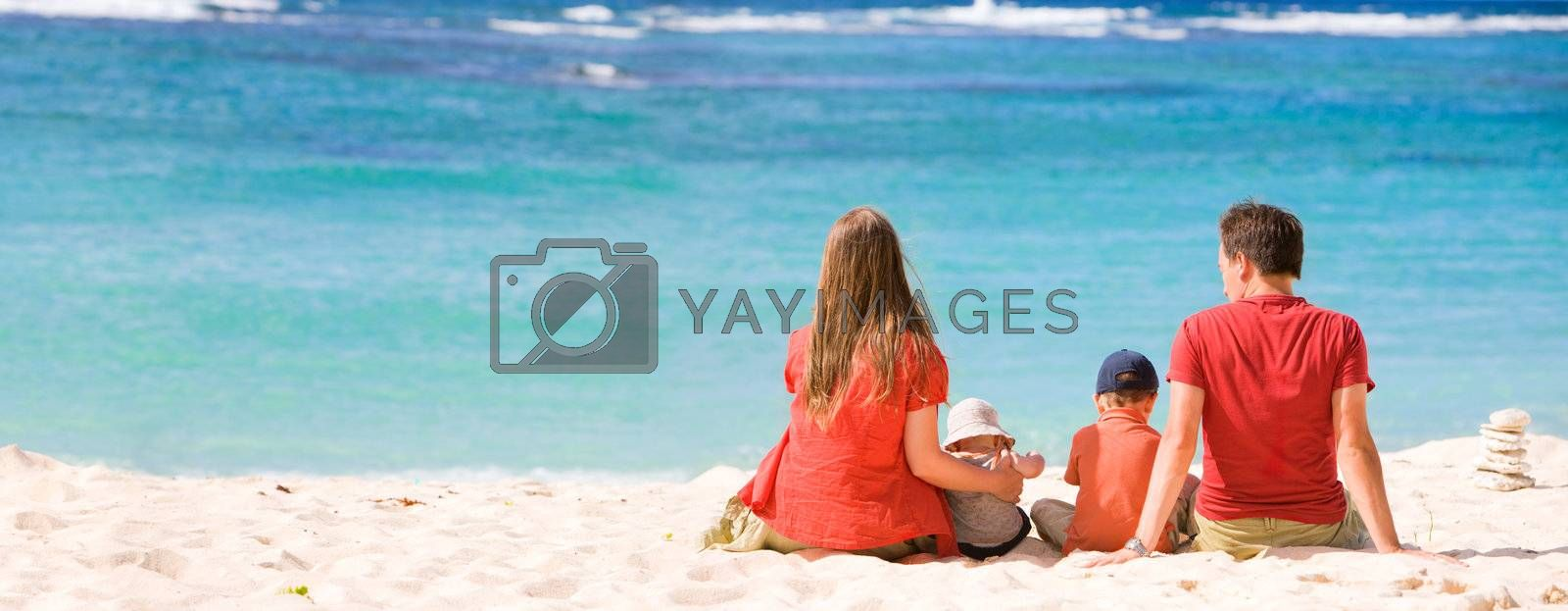 Family vacation. Young family of four in tropical paradise