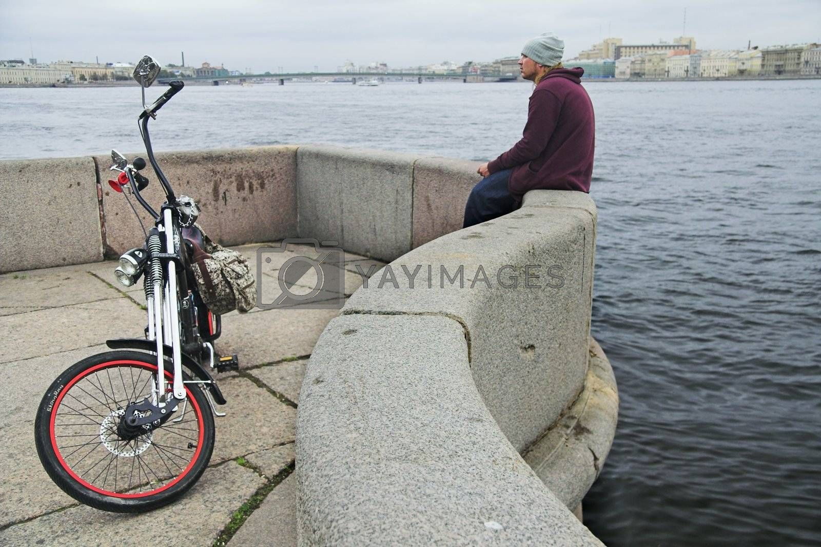 cyclist and his bicycle on granite river embankment