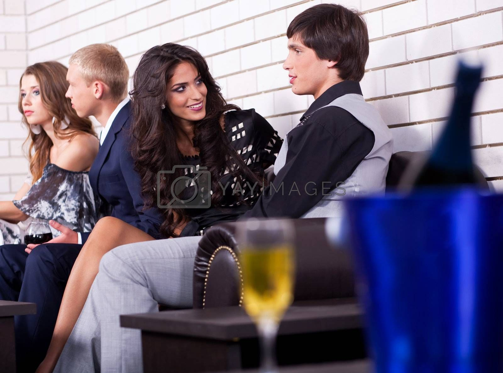 Group of people at party, sit on couch and talk
