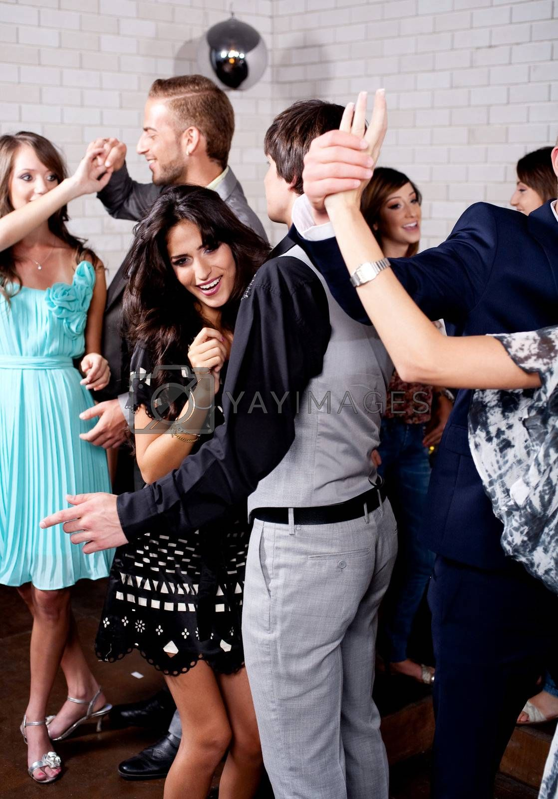 Group of many people dance at night club