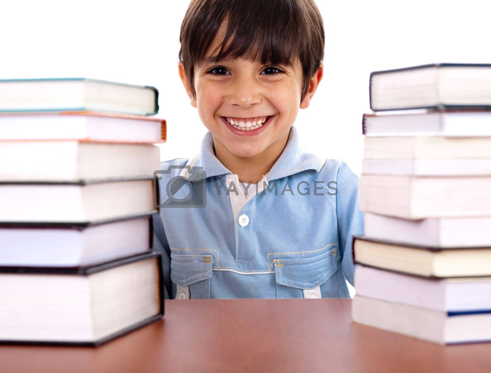Smiling young school boy surrounded by books on white background