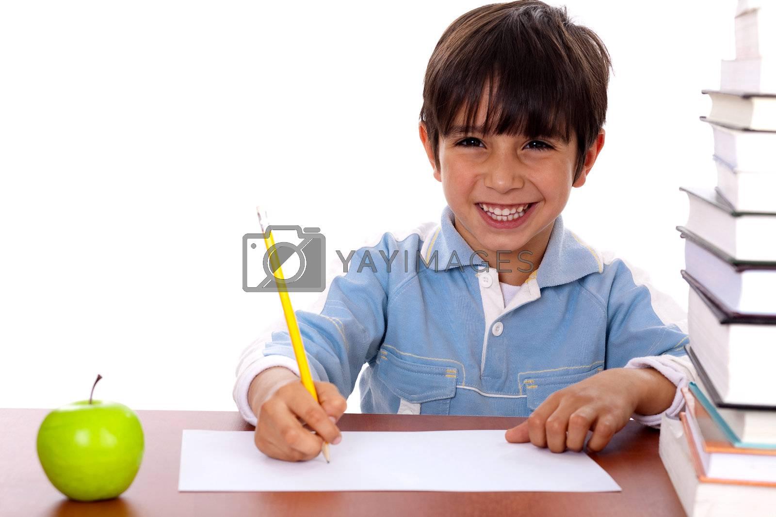 Young kid enjoying art as he draws on blank sheet of paper