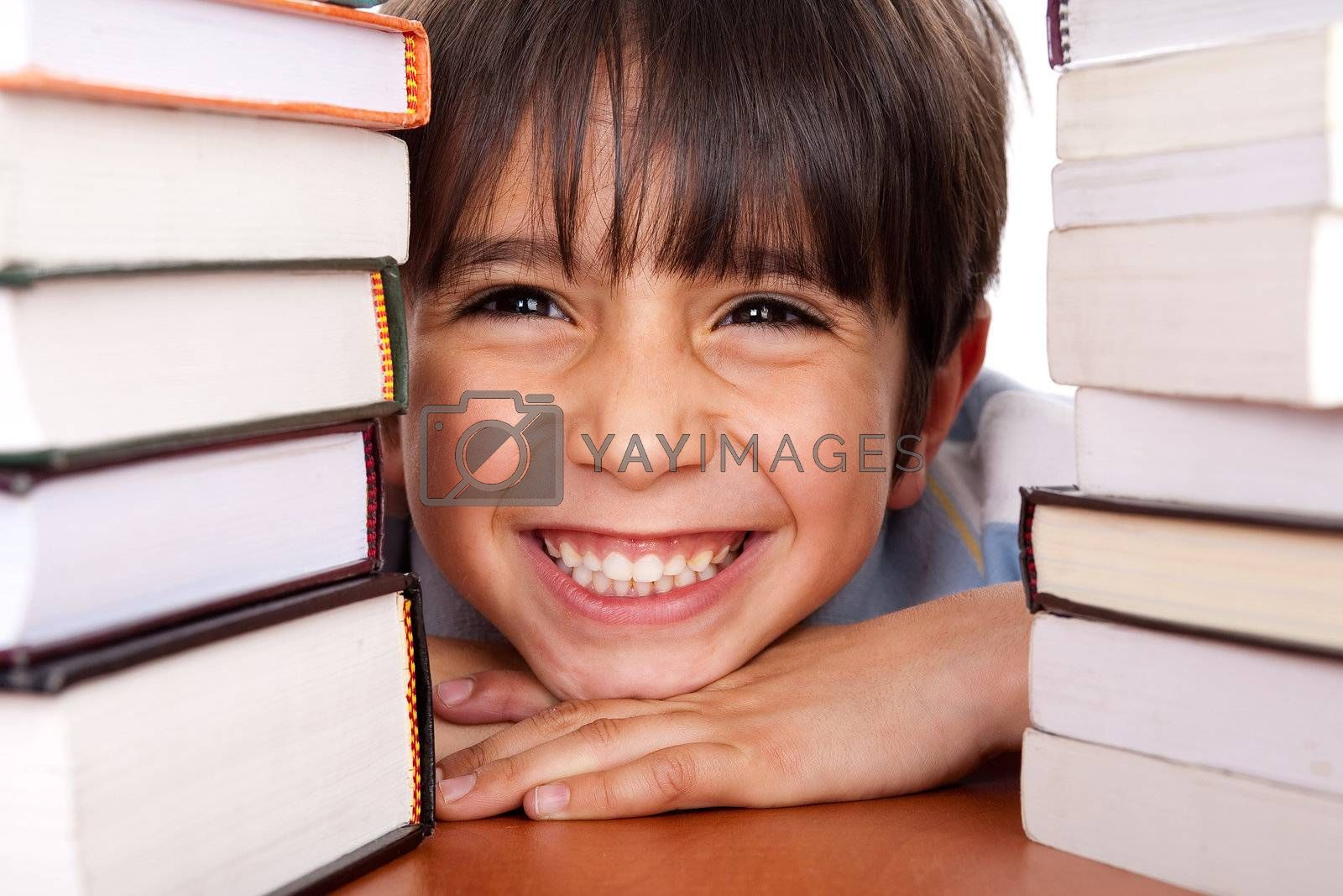 Young boy smiling at camera as he relaxes on table piled up with books