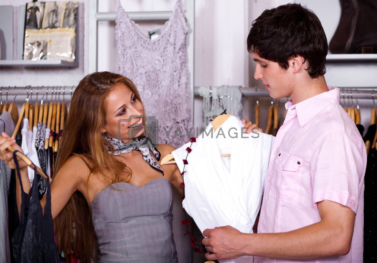 Portrait of young couple looking at fashionable cloths during sale