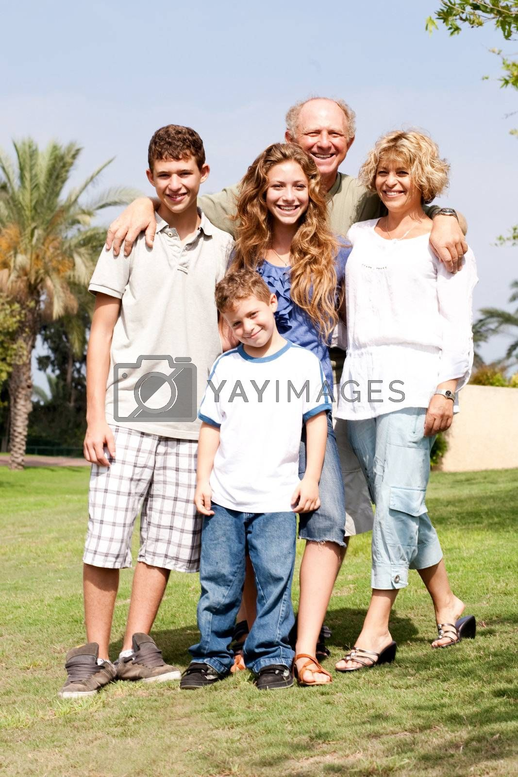 Grandparents with their children posing in the park, outdoors