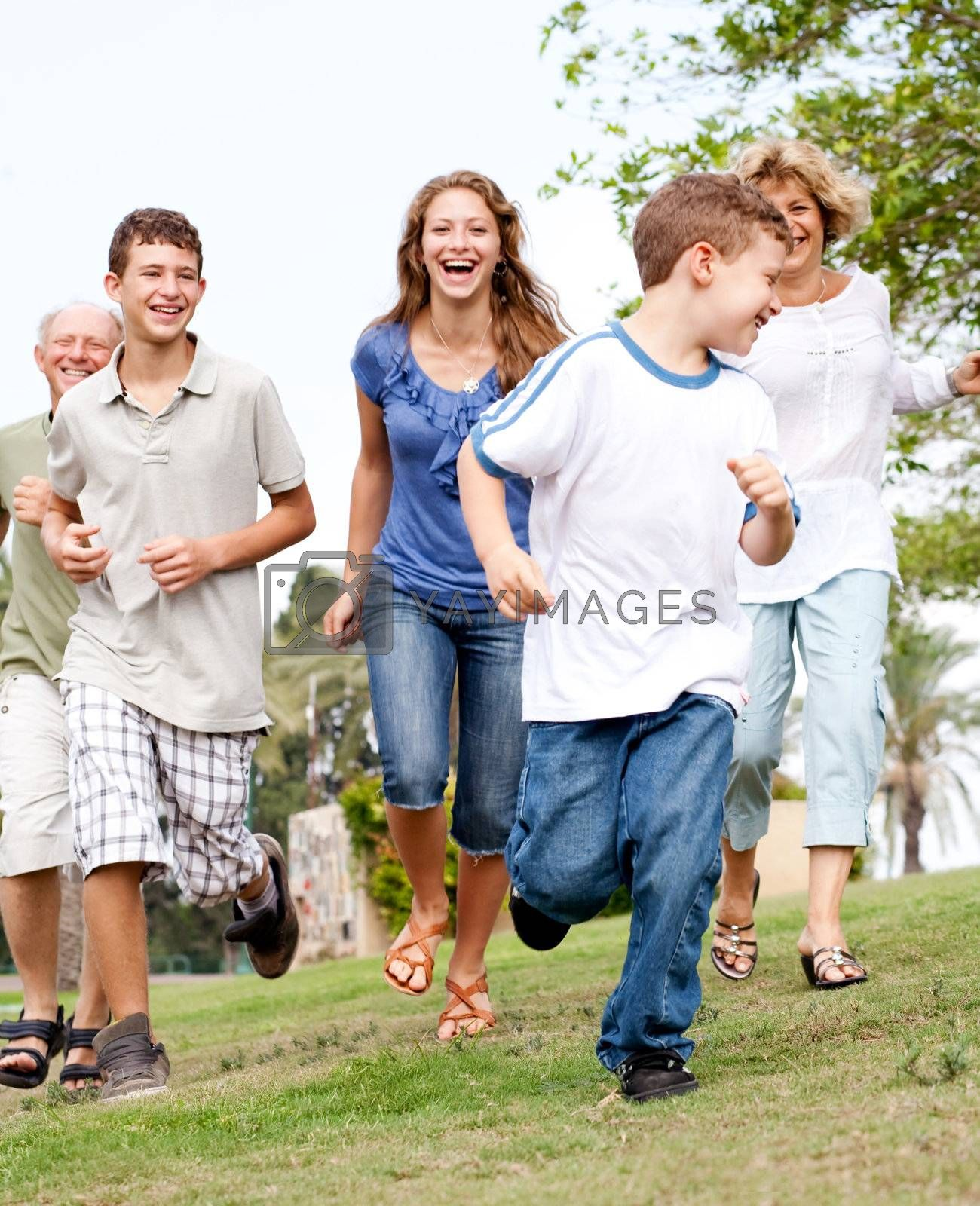 Happy young family chasing young kid in the park and having fun