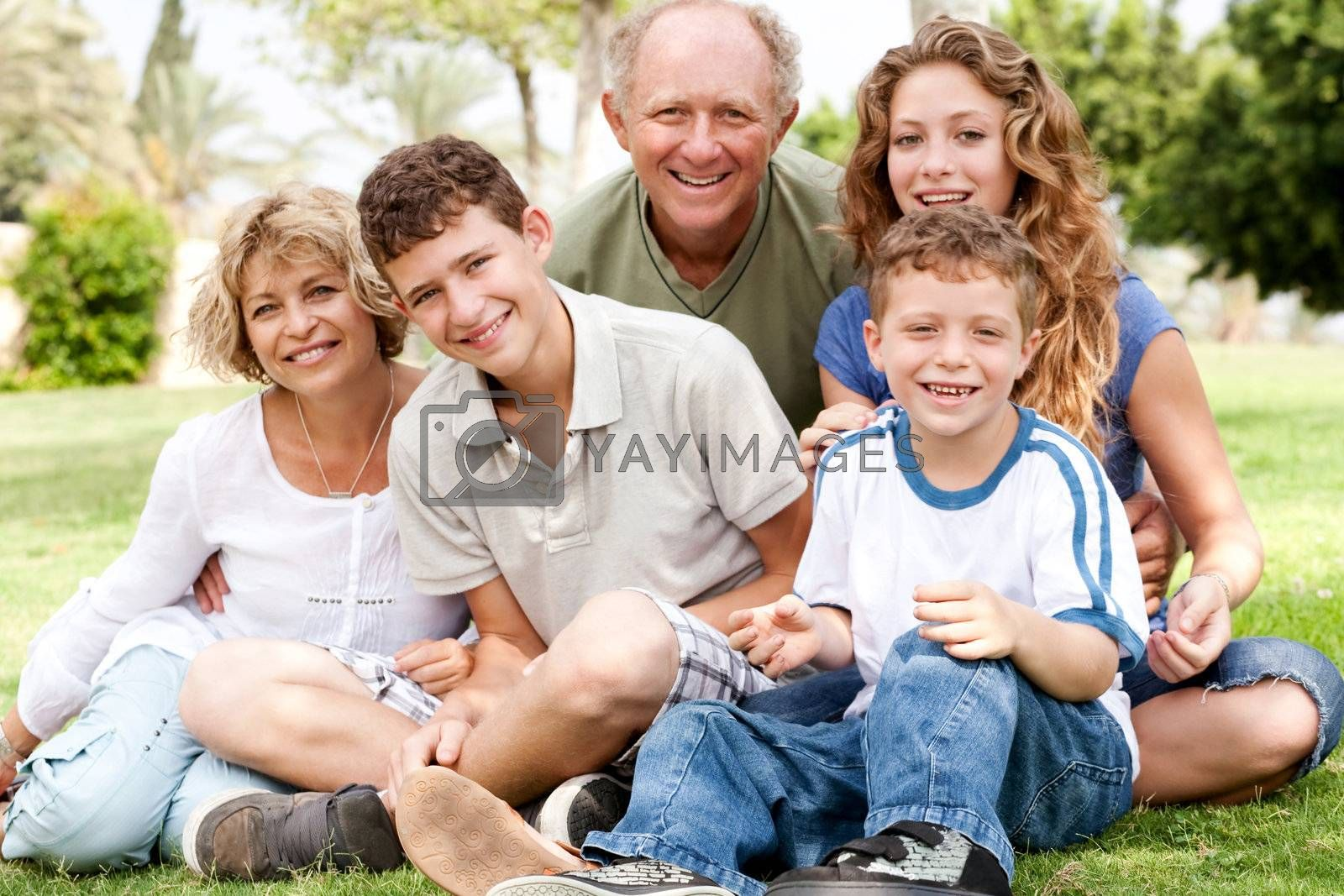 Portrait of happy family of five smiling at camera, relaxing in park