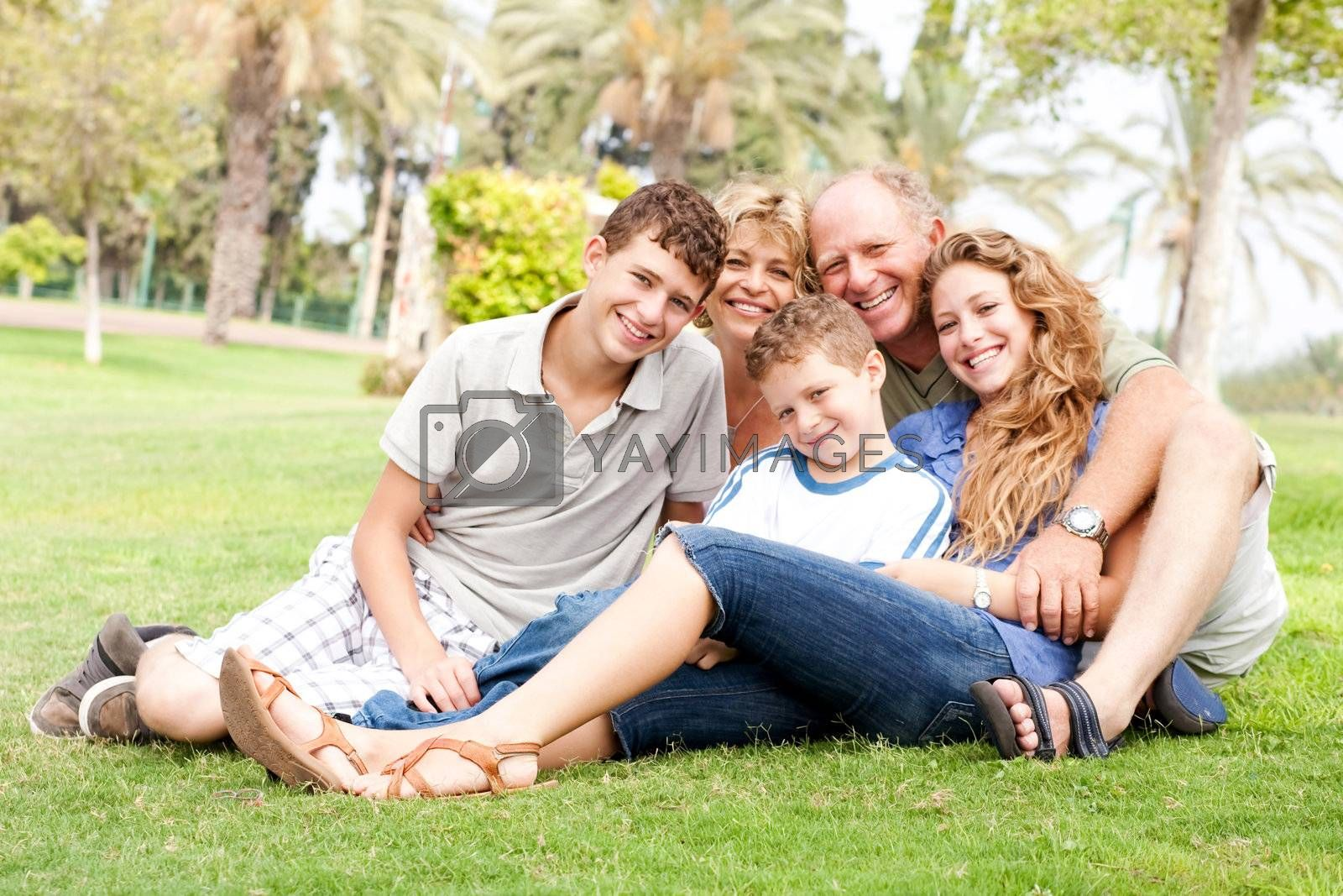 Family of five relaxing on sunny day in the park and smiling at camera