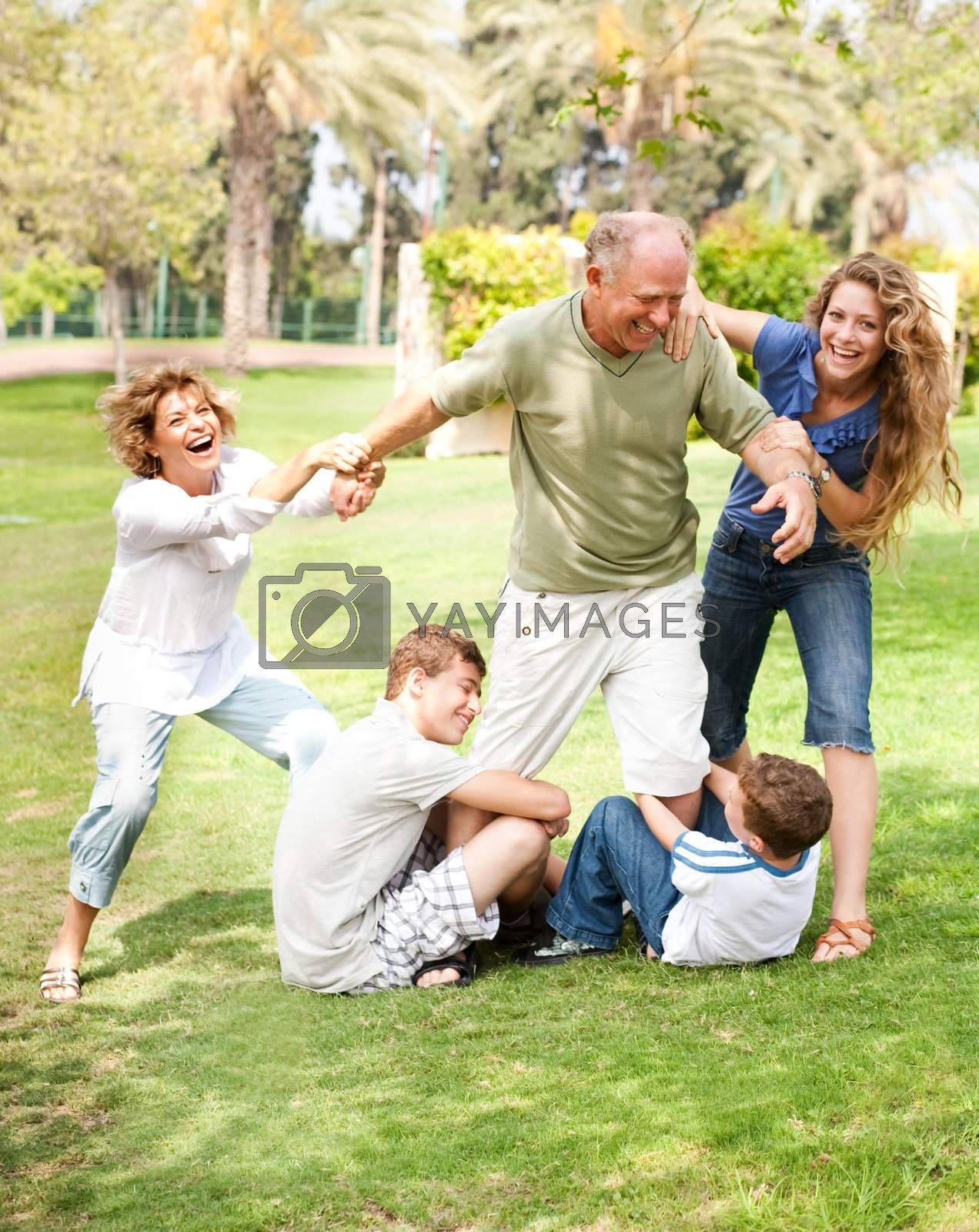 Family members holding back grandfather and having fun