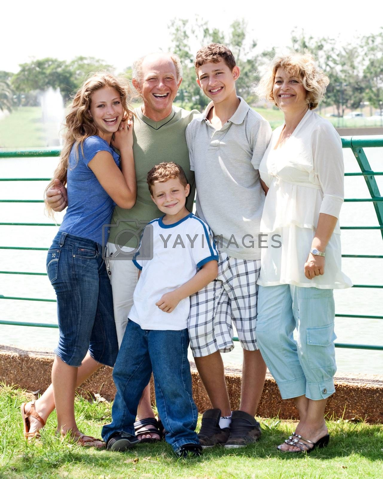 Happy family posing infront of the lake on a sunny day