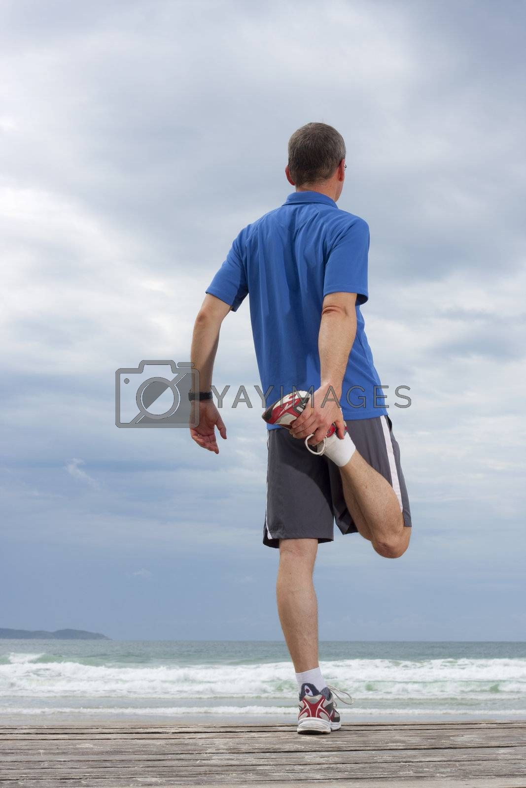 Runner doing stretching exercise on a beach