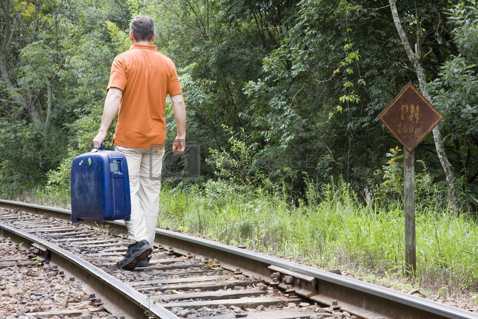 Man with suitcase walking on a railway in Brazil