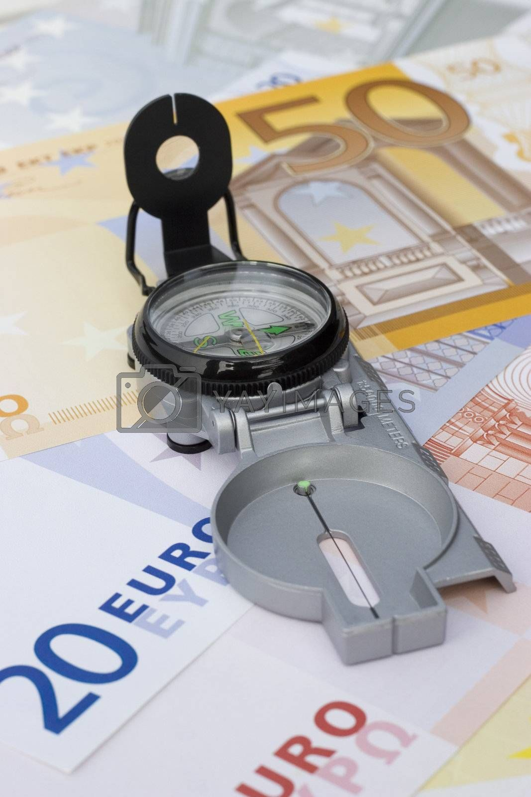 Compass on euro banknotes. Focus on the compass