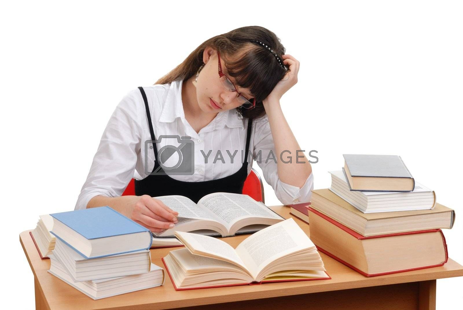 Teenage girl sitting behind a desk and reading a book