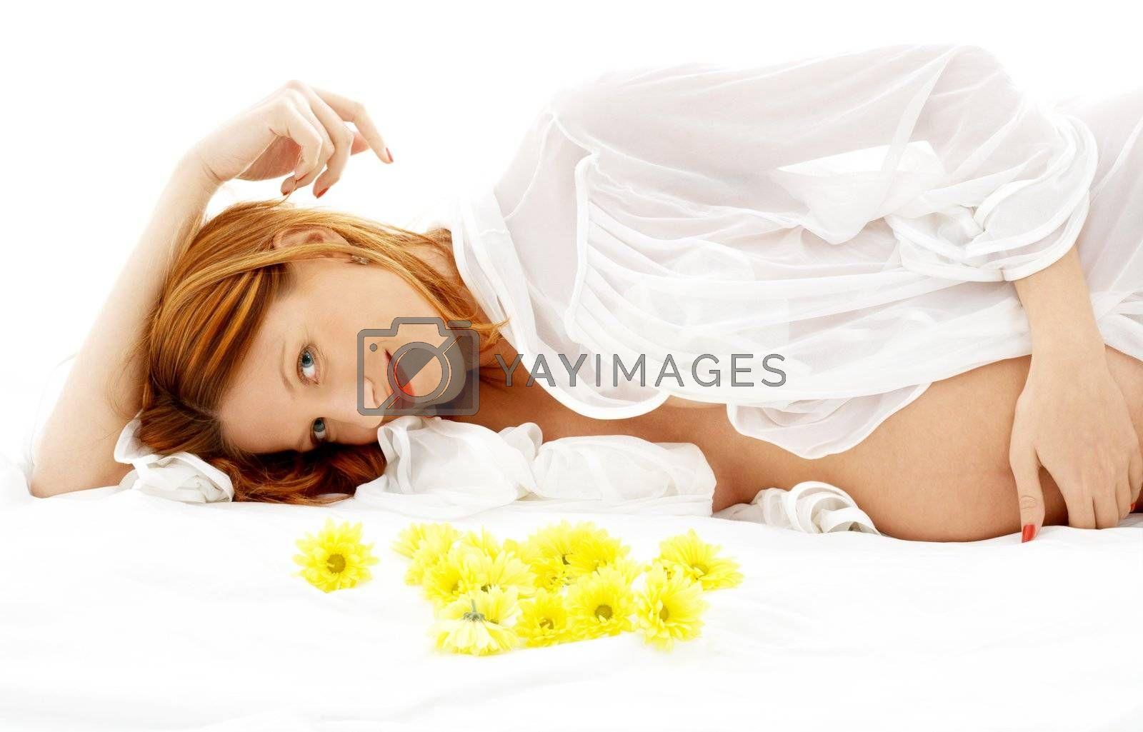 beautiful pregnant woman with yellow flowers in bed