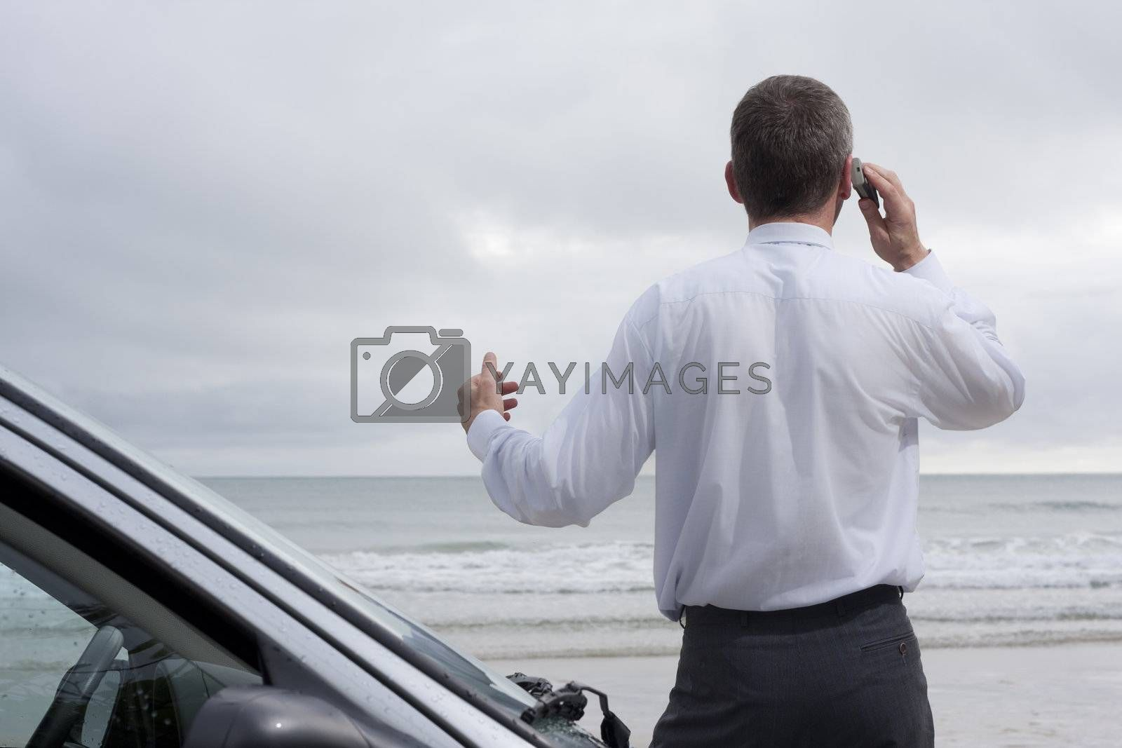 Royalty free image of Businessman talking on cell phone at the sea by ArtmannWitte