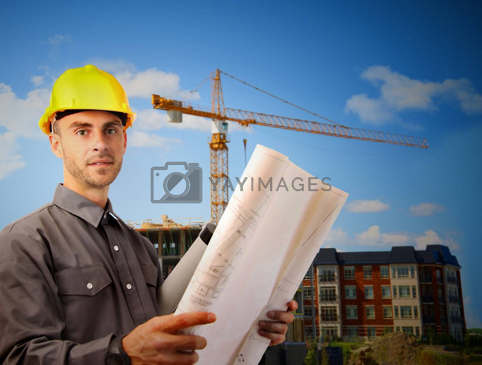 Young architect wearing a protective helmet in front of a building site