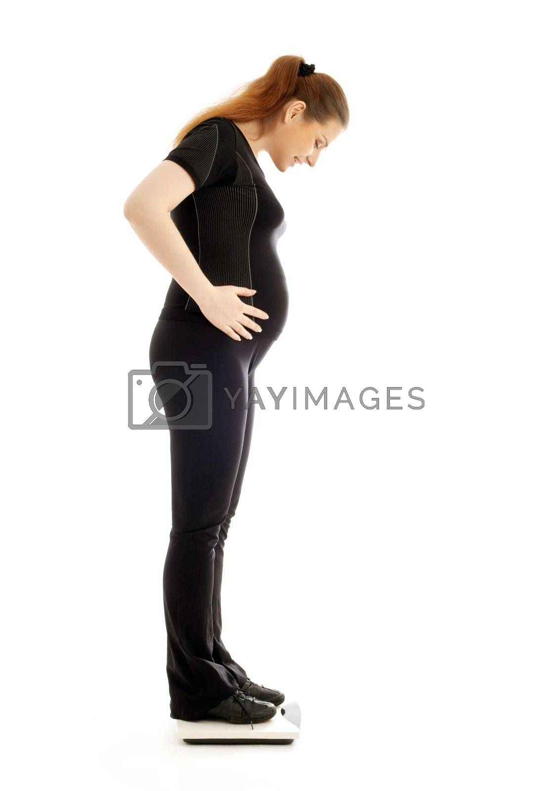 lovely pregnant lady weighing oneself over white background