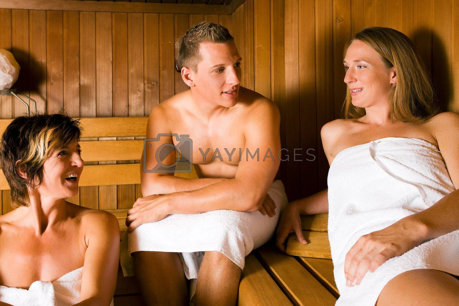 Three people (one male, two female) relaxing in a sauna, doing a lot for their health but also having fun with it