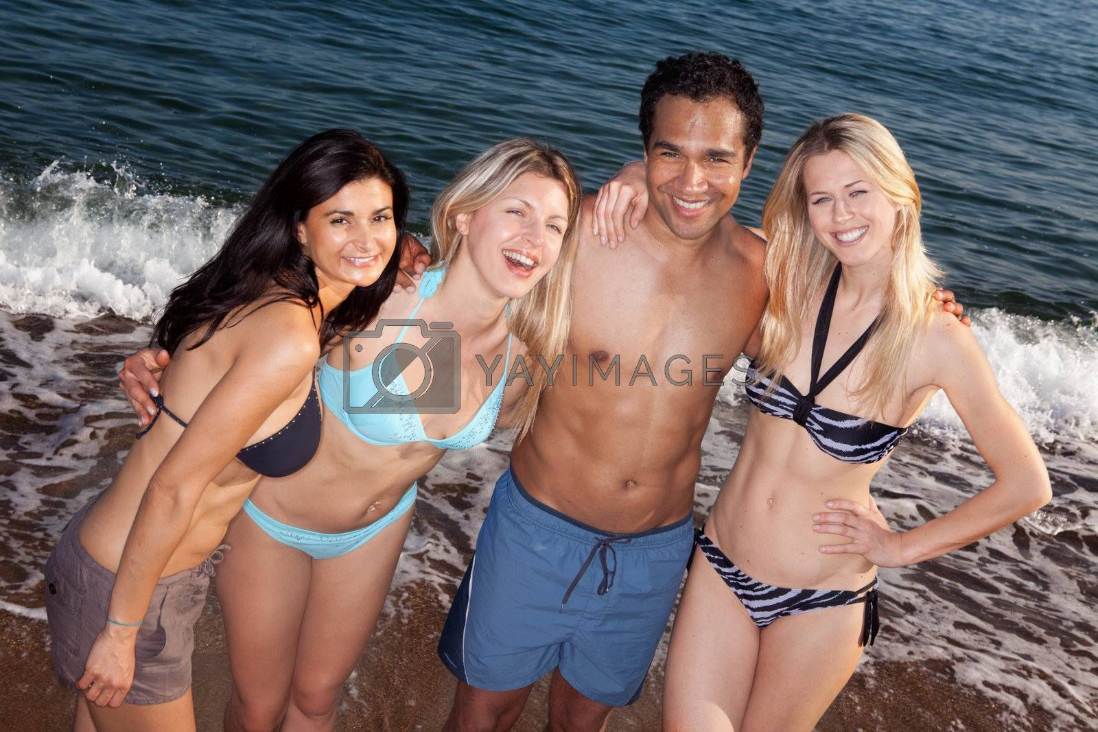 A group of friends smiling having fun at the beach