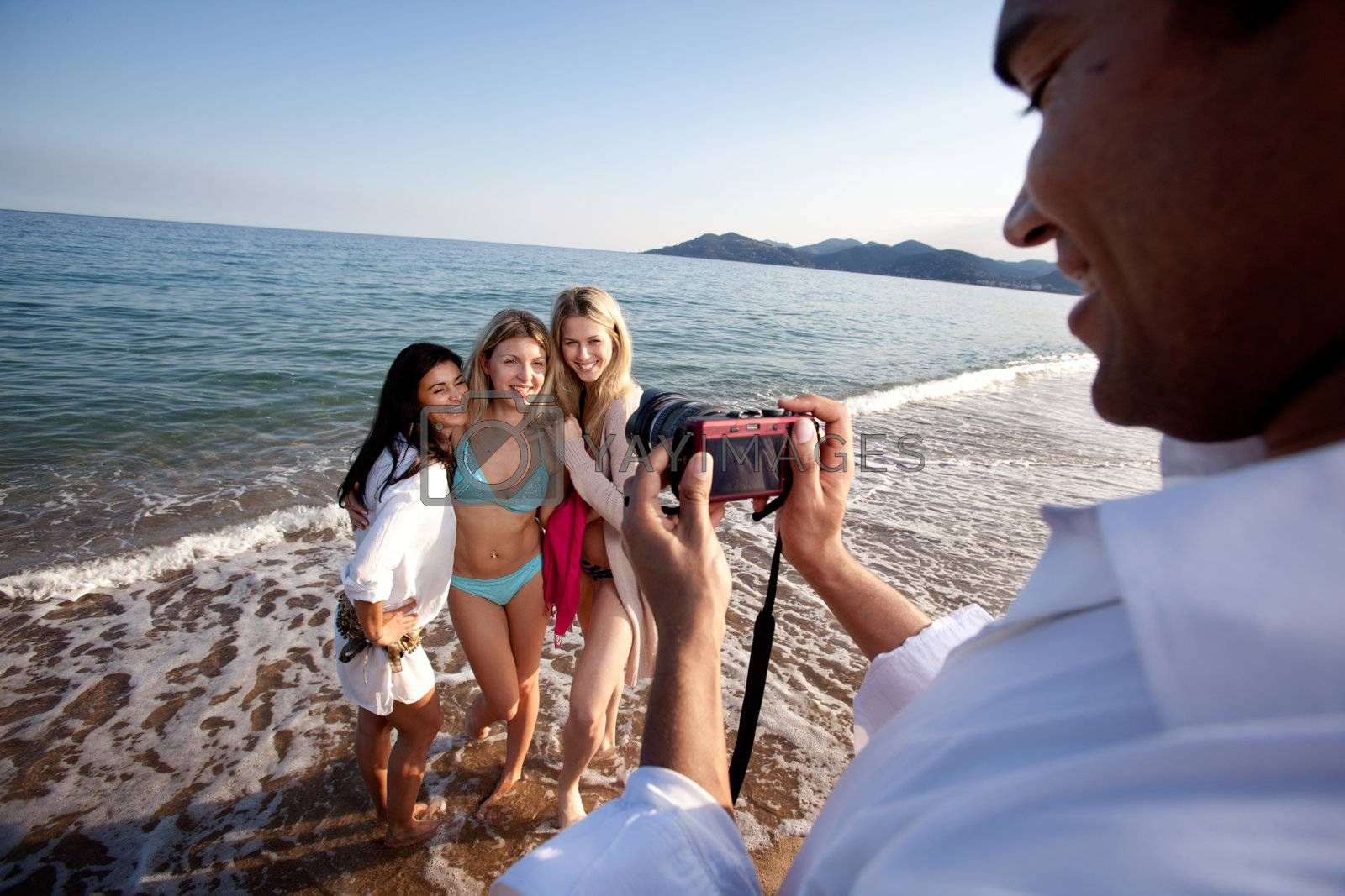 A man taking a photo of three women at the ocean.