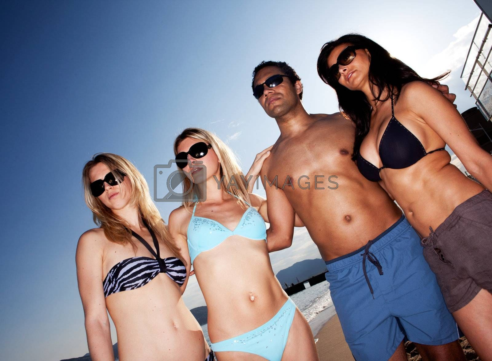 A group of models on the beach against a blue sky