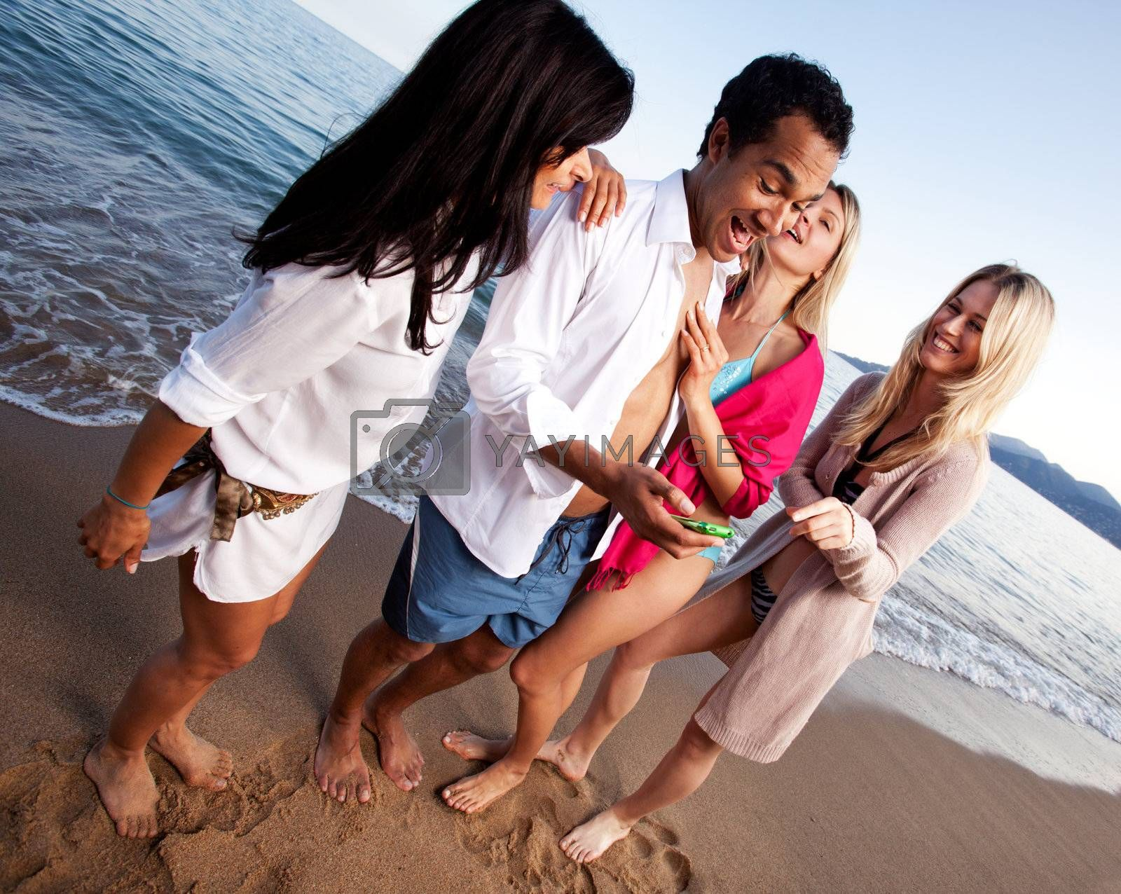 A group of friends having fun at the beach, looking at a cellphone