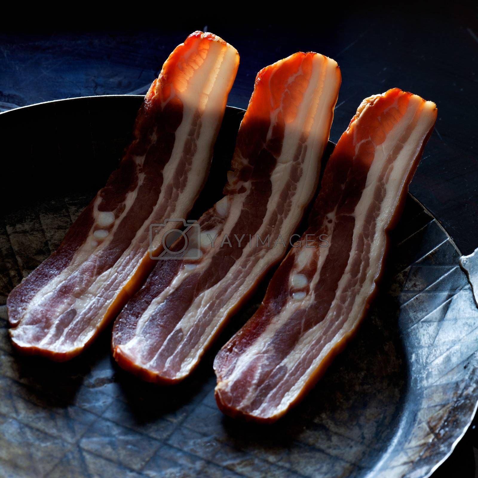 three stripes of bacon in a pan by bernjuer