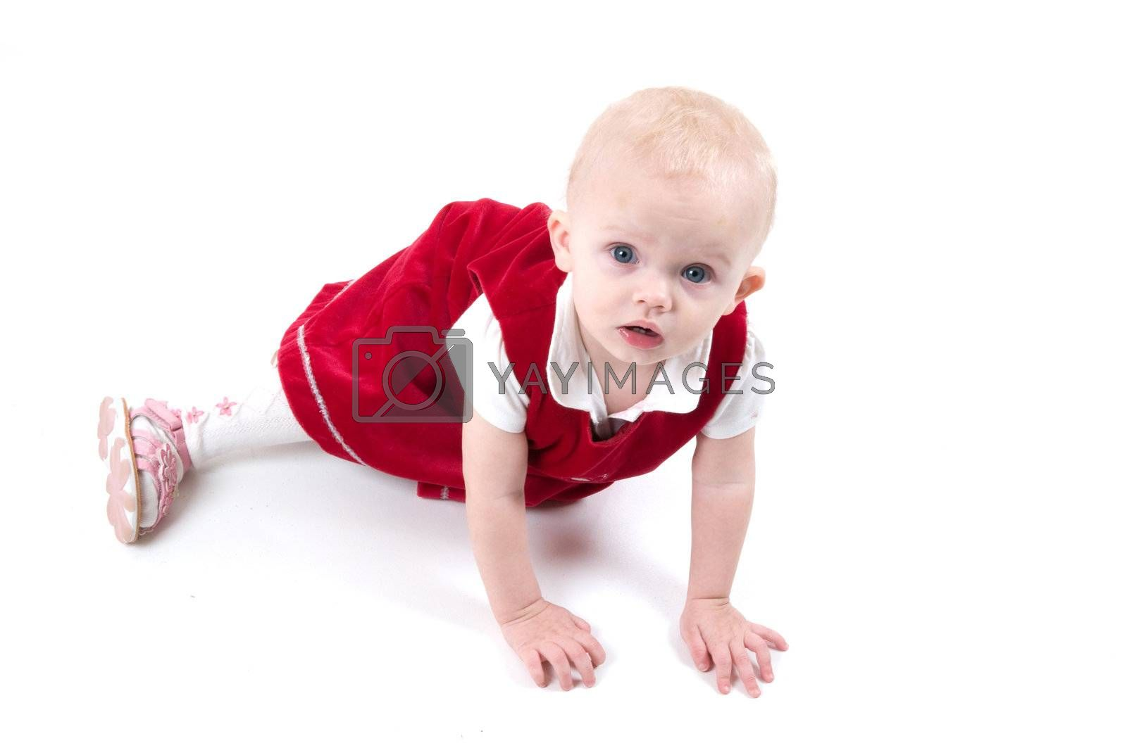 Baby in red is sitting on the floor