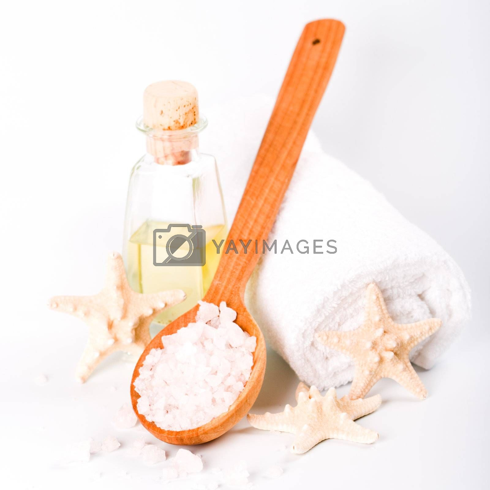 spa products: sea salt on wooden spoon, towel, oil and star