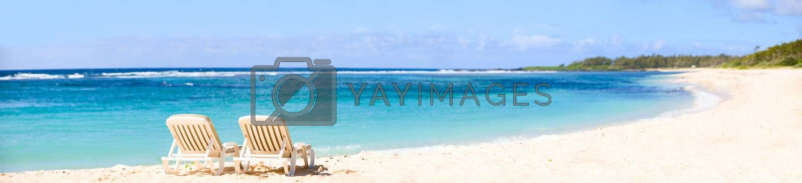Tropical Paradise. Panorama of tropical white sand beach with sun beds.