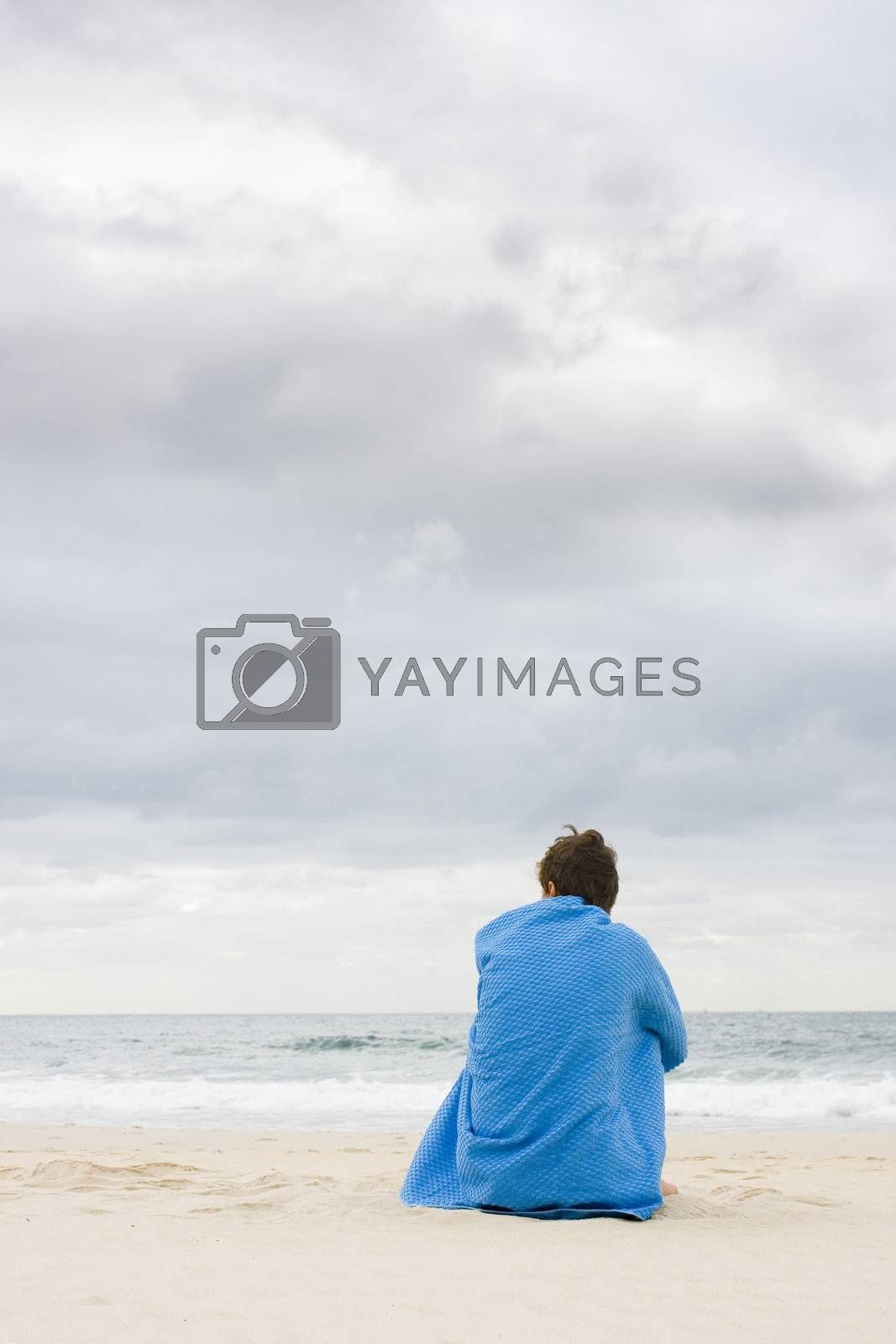 Woman sitting on a beach beneath a wide cloudy sky covered with a blue towel