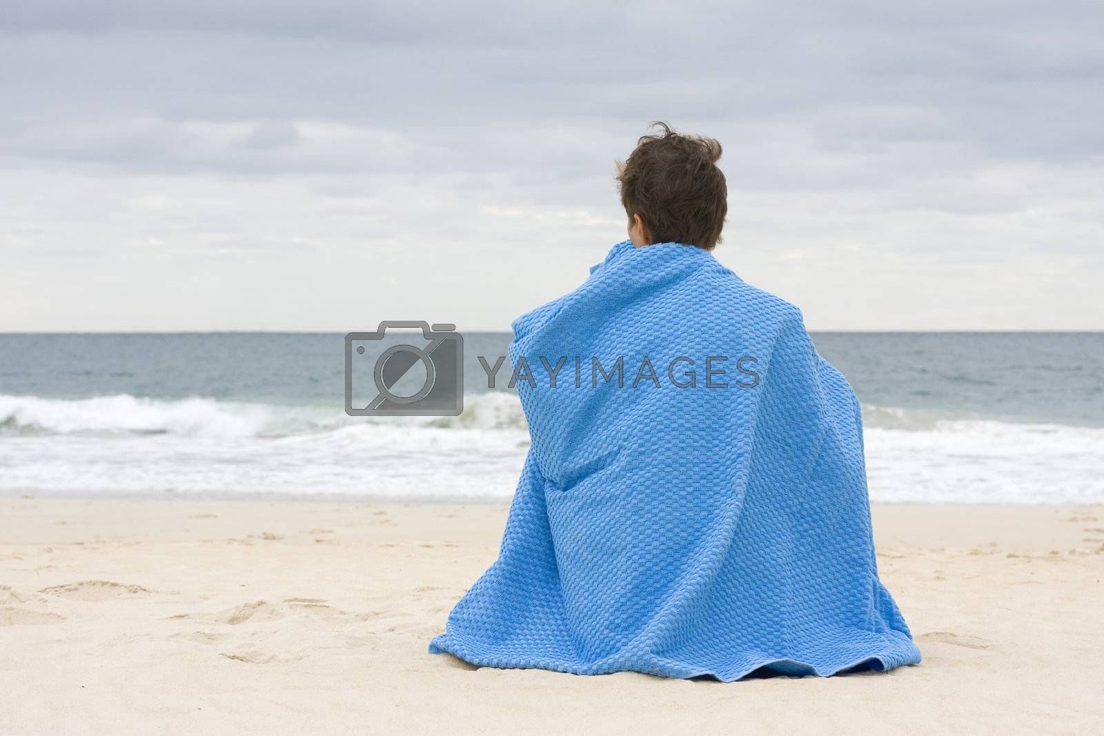 Woman sitting on the beach on a cloudy day